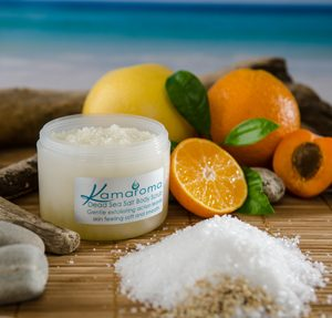 Dead Sea Salt Body Scrub – Moisturising Exfoliator for Smooth, Soft Skin pictured with a halved mandarin and apricot and while grapefruit and orange with a blue seascape in the background.