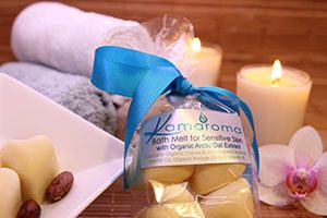 Organic Bath Melts for Sensitive with an orchid, lighted candle and rolled face cloths in the background.