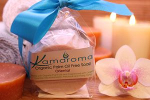Organic Oriental Palm Oil Free Soap round inside paper wrapper and placed inside a cellulose bag tied with a turquoise blue ribbon with an orchid, lighted candle and rolled face cloths in the background.