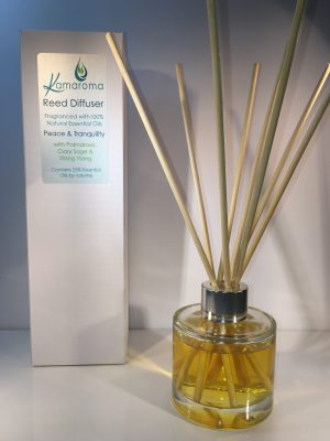 Reed Diffuser with blend of essential oils to give a sense of peace and tranquility pictured with rattan reeds inside the bottle with box in background.