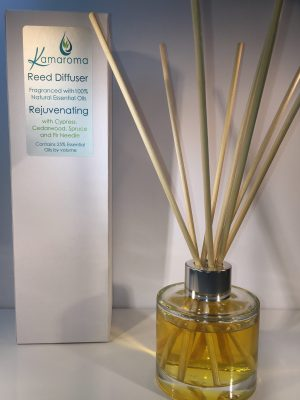 Reed Diffuser with a rejuvenating blend of essential oils pictured with rattan reeds inside the bottle with box in background.