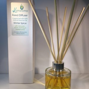 Aromatherapy reed diffuser with a warm winter spice fragrance made from 100% essential oils pictured in use with rattan reeds in the bottle and the box in the background